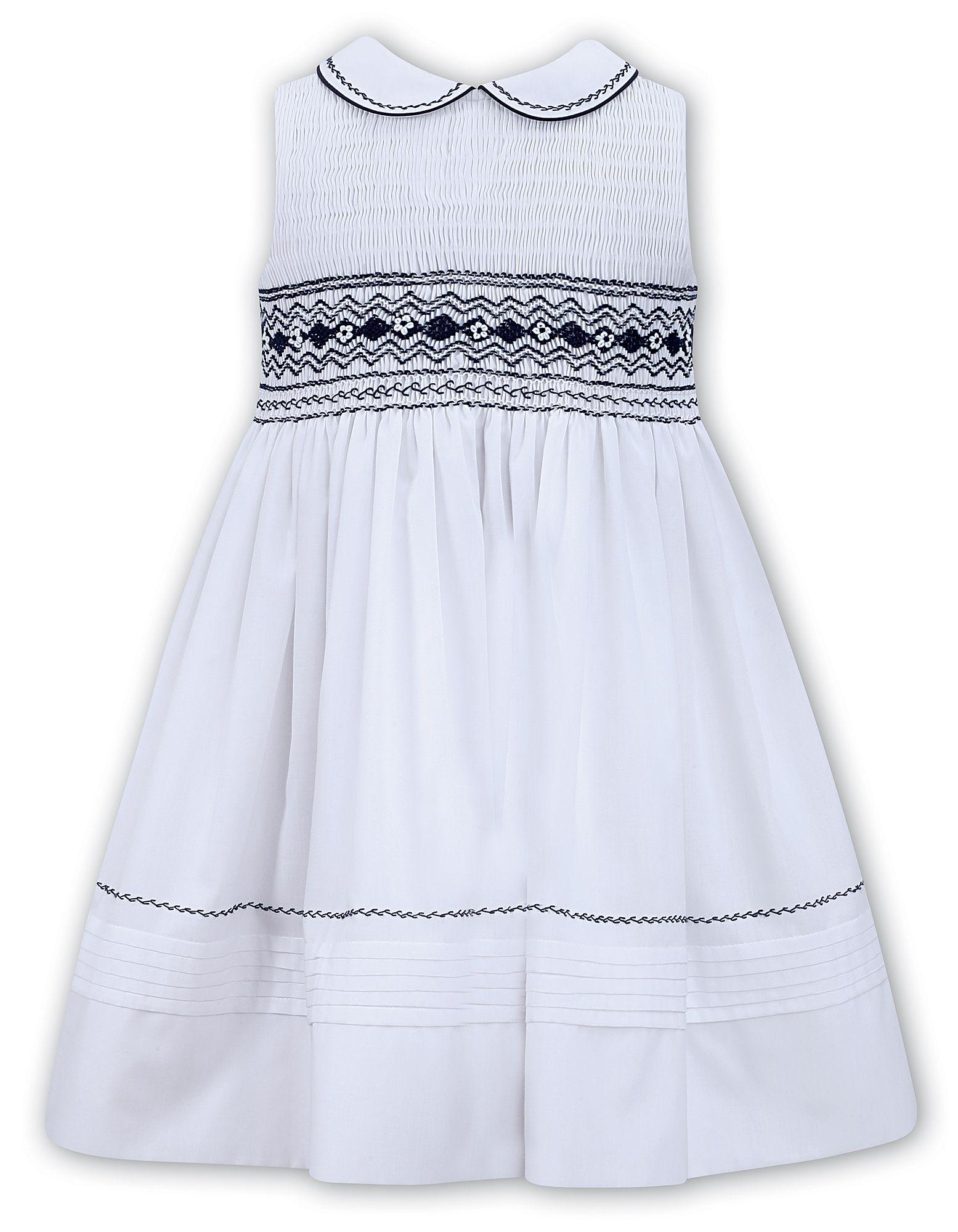 e1f5ccfa4f0 Sarah Louise Sleeveless White Dress With Full Smocked Top Navy Detaili